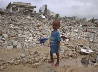 A Somali child from southern Somalia stands in the rubble of a destroyed building near a refugee camp in Mogadishu, Somalia, Tuesday, Aug 9, 2011.