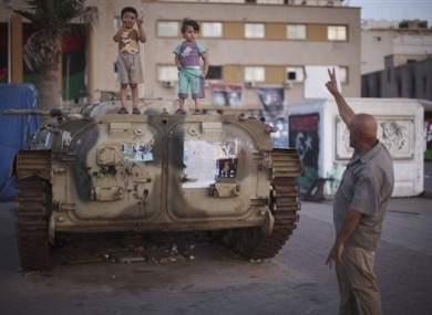 A man asks two kids, over an armored car, to make the victory sign at the rebel-held town of Benghazi, Libya, Tuesday, Aug. 10, 2011.