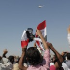 Anti-Mubarak protesters chant slogans as a helicopter carrying Egypt's ousted president flies over them ahead of his trial on charges of corruption and ordering the killing of protesters during the uprising. (AP Photo/Nasser Nasser)