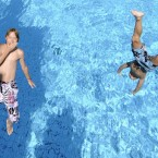 Two friends jump into a cool public pool in Gelsenkirchen, Germany, on a hot day. (AP Photo/Martin Meissner)