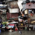 Chest-deep floodwater submerges suburban Quezon City, north of Manila, Philippines. (AP Photo/Pat Roque)
