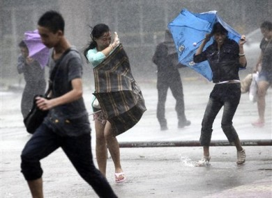 People brave strong winds and rain on a street as a typhoon hit Haikou in south China's Hainan province, Thursday, Sept. 29, 2011.