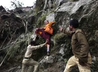 Members of Indian Army help a Buddhist monk to descend a huge landslide following Sunday's 6.9 magnitude earthquake in Sikkim, India.