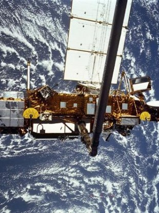This is the STS-48 onboard photo of the Upper Atmosphere Research Satellite (UARS) in the grasp of the RMS (Remote Manipulator System) during deployment, from the shuttle in September 1991.