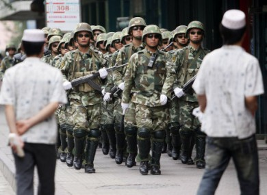File photo: Uighur men, foreground, watch as a formation of paramilitary police officers patrol Urumqi in western China's Xinjiang region.