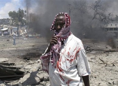 A wounded man stands at the scene of an explosion in Mogadishu, Somalia, Tuesday, Oct. 4, 2011.