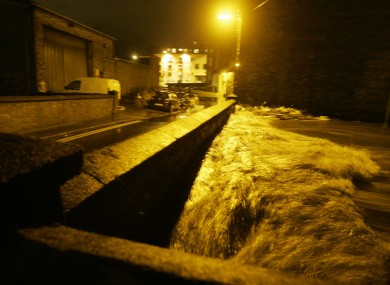 The Camac River reaches the top of a bridge on Tower Terrace on Monday night after hours of intense rain.