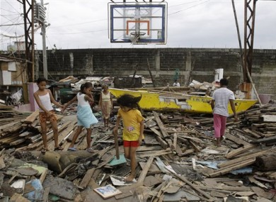 Residents walk on debris from damaged houses and a boat along a coastal village in Navotas, north of Manila, Philippines on Sunday Oct. 2, 2011.