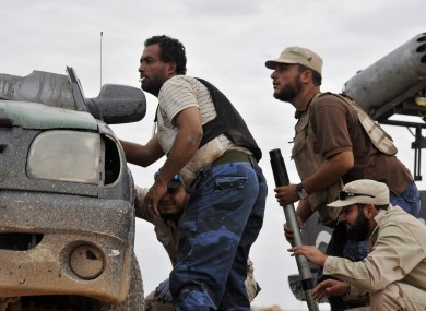Libyan revolutionary fighters take cover outside the city of Sirte yesterday