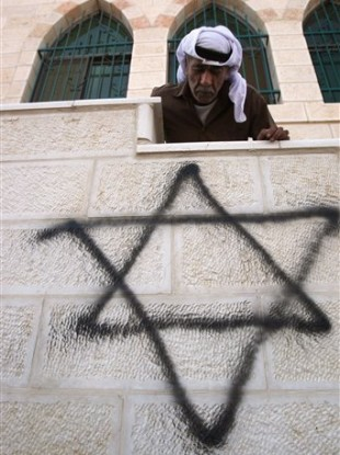 A Palestinian man looks down on a graffiti of the Star of David spray painted on a wall of a mosque torched and vandalized by arsonists in the West Bank village of Qusra, near Nablus, Monday, Sept. 5, 2011.