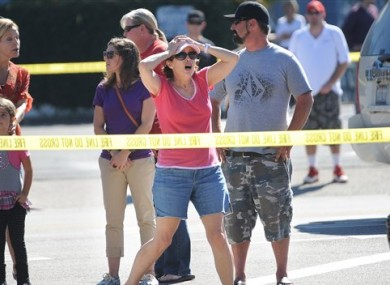 Onlookers react near the site where eight people were killed and three were wounded in a shooting at a hair salon in Seal Beach, Calif., Wednesday, Oct. 12, 2011.