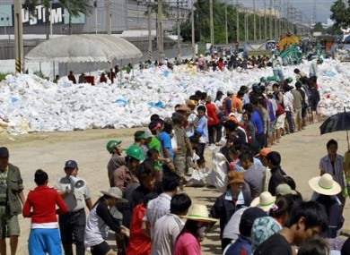 Factory workers join hands in stacking sandbags to make flood barriers at Nawa Nakorn industrial district on the outskirts of Bangkok, Thailand Sunday, Oct. 16, 2011.
