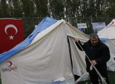 An unidentified earthquake survivor fixes his tent in a tent city set up in a soccer field in Ercis, Van.