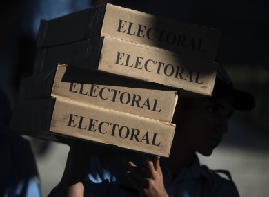 A police officer carries boxes filled with ballots