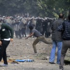 Protesters throw stones at Egyptian riot police near the interior ministry in downtown Cairo, Egypt, today. (AP Photo/Khalil Hamra/PA Images)