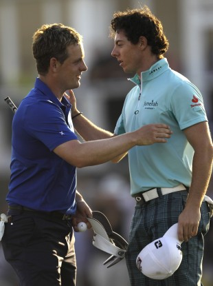 Luke Donald, left, and Rory McIlroy shake hands after they finished the first round of Dubai World Championship earlier.