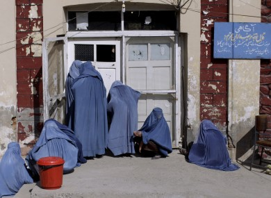 File photo: Afghan women peek inside a hospital while she and others wait for an employee to let them enter, on the outskirts of Kabul, Afghanistan