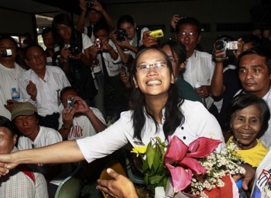 Nilar Thein, center, an activist of the 88 Generation Students Group, shakes hands with one of her colleagues as she arrives at Rangoon airport after released from Theyet prison