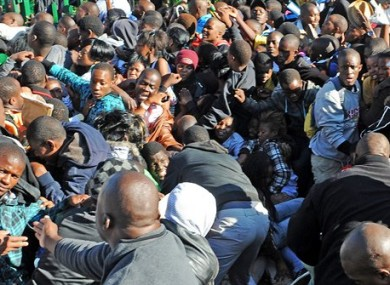 Thousands of young students and their parents push their way into the gates causing a stampede at the University of Johannesburg