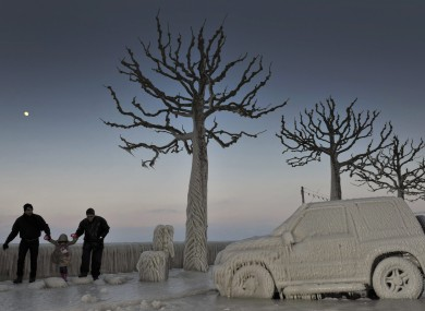 People walk along an icy promenade past ice covered cars and trees on the shores of Lake Geneva in Versoix, Switzerland on Sunday
