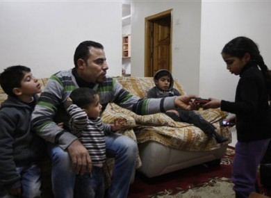 Palestinian Hussein al-Ustaz sits with his children in his house in the West Bank village of Bir Naballah on 4 February 2012.