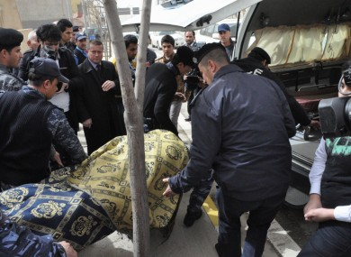 The body of the slain American gym teacher is carried out of the school in Sulaimaniyah