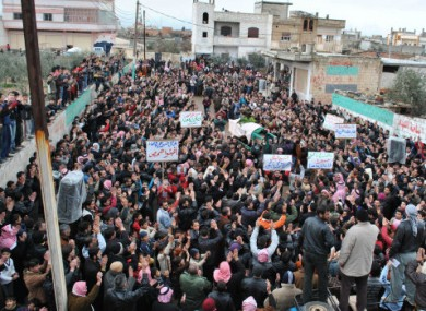Mourners at a funeral in February in the Rastan neighbourhood of Homs carry signs telling the people in Baba Amr to