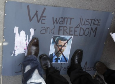 Protesters stand on a crossed picture of Syrian President Bashar Assad during a rally against his regime in front of