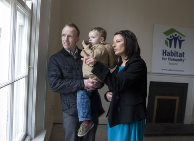 Parents Keith Greene and Jennifer Clail with their son Nathan aged 3yrs from the window of their new home in Inchicore, Dublin, which has been renovated by Habitat for Humanity Ireland in partnership with Dublin City Council.