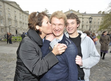 Myles McCormack from Rathmines, one of Trinity College's new scholars, is congratulated by his mother Philippa and brother Conor in the front square of Trinity College today.