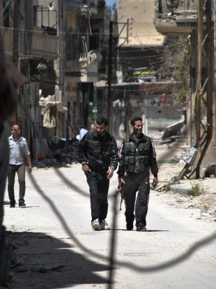 Free Syrian Army fighters walk on street in Khaldiyeh neighborhood in Homs, Syria