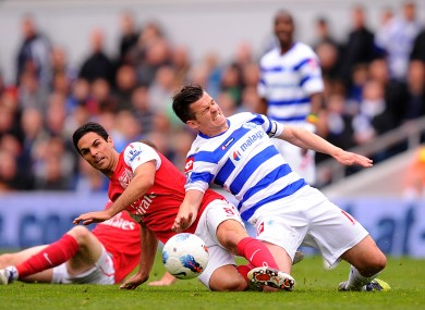 Mikel Arteta slides in to win the ball from QPR's Joey Barton