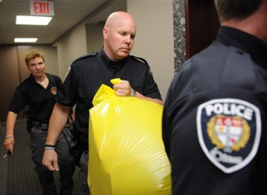 Police remove a package from the Conservative Party offices in Ottawa yesterday.