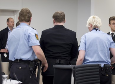 Breivik, centre, is escorted from the courtroom by police following the incident