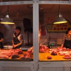 Butchers sell fresh meats in competing stalls at a farmer's market in Beijing, China.   Image: peikwen