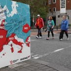 People walk past a defaced sign against the European Fiscal Treaty in Dublin, ahead of tomorrows referendum.   Niall Carson/PA Wire