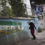 An Iranian woman walks past the former US embassy in central Tehran.   Image: Morteza Nikoubazl