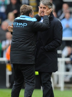 Manchester City manager Roberto Mancini celebrates with one of his backroom staff.