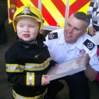 Dylan being awarded his plaque by Naas firemen.