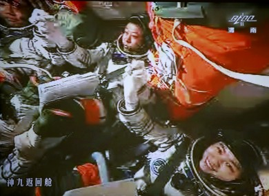The three astronauts celebrate after the successful docking between the spacecraft and the lab module