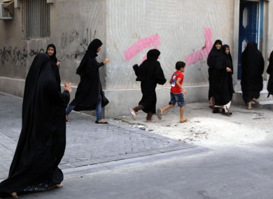 Women and children run as riot police, unseen, chase Bahraini anti-government protesters