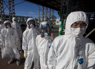 File photo (2011) shows workers in protective suits and masks wait to enter the emergency operation center at the crippled Fukushima Dai-ichi plant