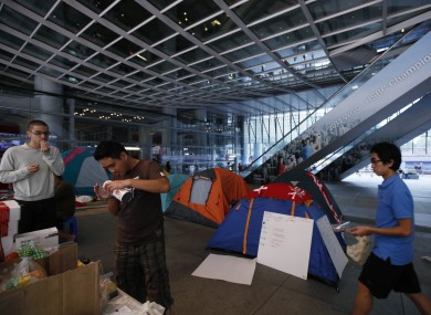 Occupy Hong Kong protestors serve snacks while sheltering under a canopy at HSBC's headquarters in the city.