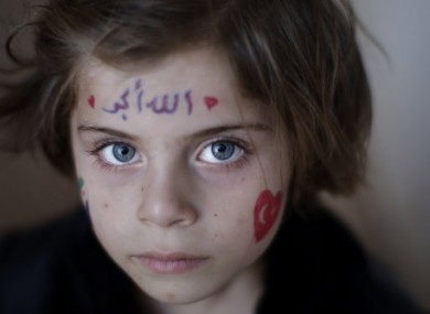 Aya Abdulhay, 5, whose family fled their Aleppo home, takes refuge at the Bab Al-Salameh border crossing in hopes of entering one of the refugee camps in Turkey.