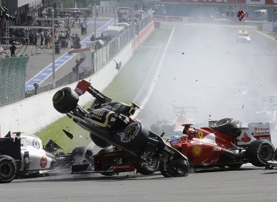 Lotus driver Romain Grosjean of France, top left, crashes with Ferrari driver Fernando Alonso of Spain, during the first lap of the Belgium Formula One Grand Prix in Spa-Francorchamps circuit.