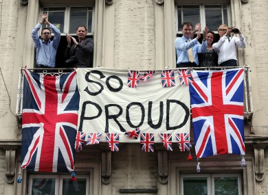Crowds cheer from windows along the route of the parade through London.