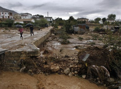 Residents walk on a muddy street after heavy rain caused flash floods in the town of Villanueva del Rosario, Malaga, southern Spain.