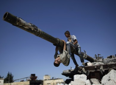 Two boys play on a Syrian military tank which was destroyed during fighting in Azaz on the outskirts of Aleppo.