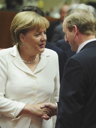 German Chancellor Angela Merkel, left, speaks with Irish Prime Minister Enda Kenny during a round table meeting at an EU summit in Brussels