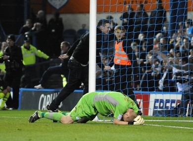 Sheffield Wednesday goalkeeper Chris Kirkland lays on the ground after been struck by a Leeds United fan.